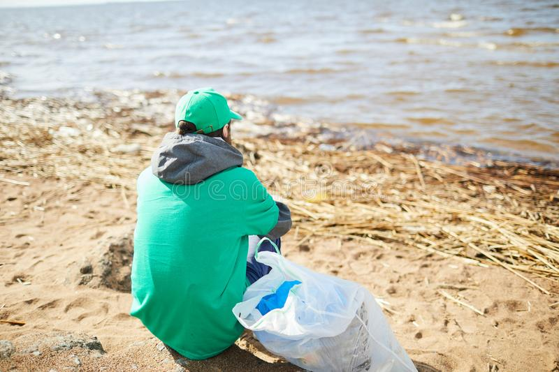 Volunteer resting on shore. Back view of volunteer in green uniform sitting on shore at plastic bag and looking away royalty free stock photography