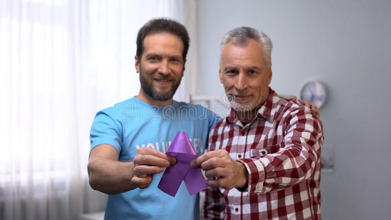 Volunteer and senior male showing purple ribbon, Alzheimer disease awareness. Stock photo stock image