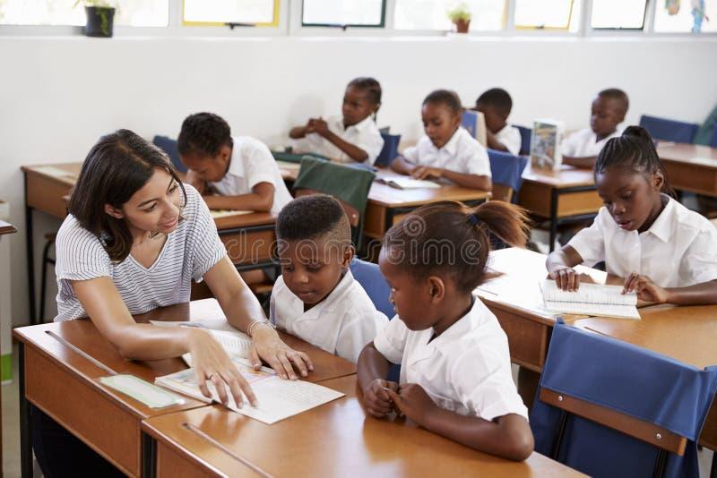 Volunteer teacher helping school kids at their desks stock photo
