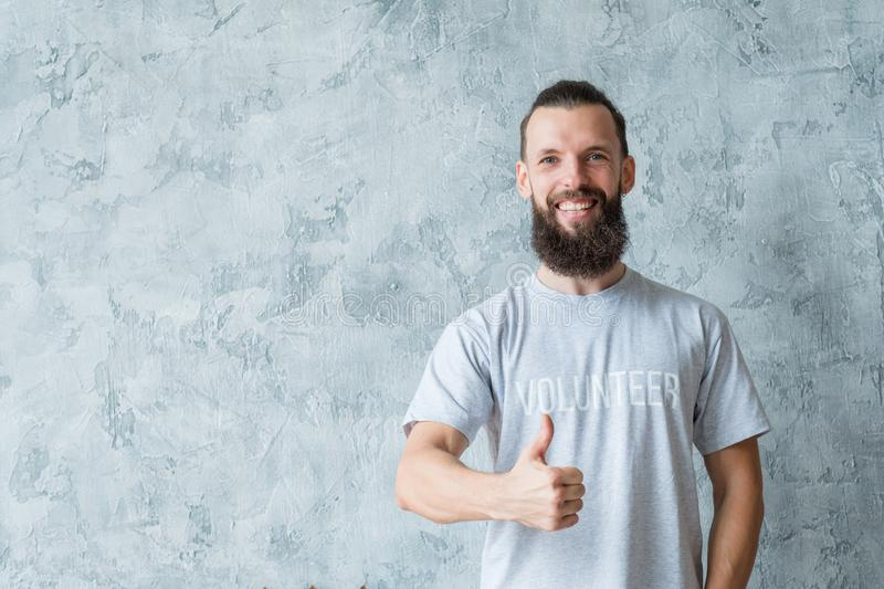 Volunteering responsible lifestyle man thumb up. Volunteering concept. Responsible lifestyle. Young smiling bearded man with thumb up. Copy space on grey royalty free stock images