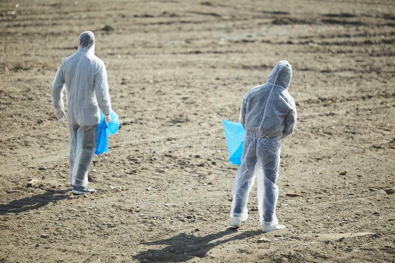 Volunteers with bags in protection costumes. Back view of two unrecognizable volunteers in protection costumes standing with blue rubbish bags royalty free stock photo