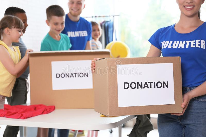 Volunteers with children sorting donation goods royalty free stock image