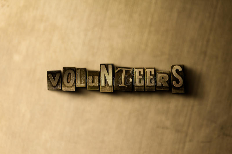 VOLUNTEERS - close-up of grungy vintage typeset word on metal backdrop royalty free stock photos
