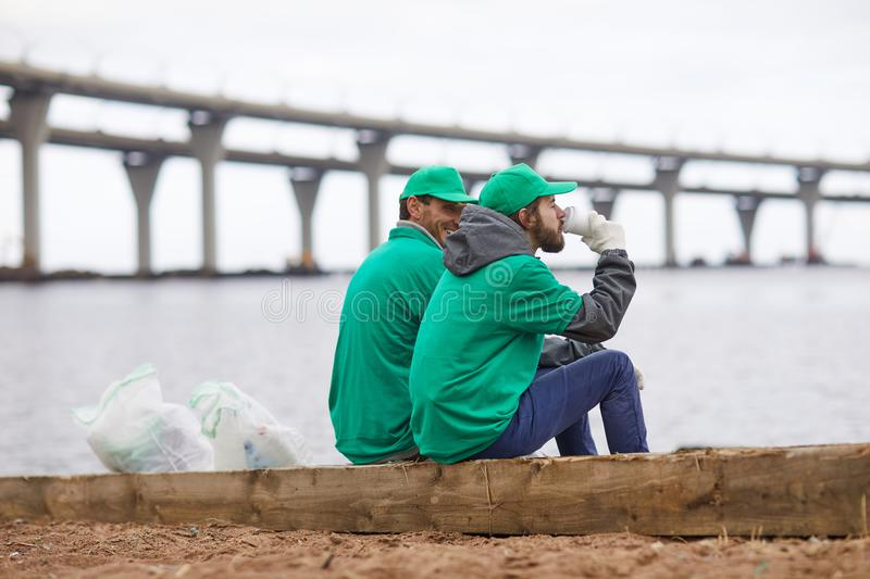 Volunteers with coffee on shore. Side view of volunteers in green uniform sitting with coffee cups and relaxing on shore royalty free stock image