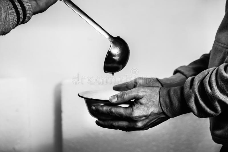 Volunteers feed the homeless. Free soup in a bowl of beggar. stock images