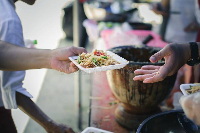 Volunteers giving food to poor people in desperate need : The concept of food sharing Help solve Hunger for the homeless.  royalty free stock photo