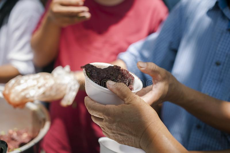 Volunteers giving food to poor people in desperate need : The concept of food sharing Help solve Hunger for the homeless.  royalty free stock images