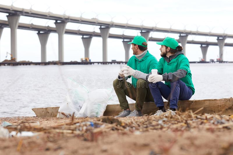 Volunteers with paper cups on shore. Volunteers in green uniform sitting with paper cups and looking away while resting on shore royalty free stock photography