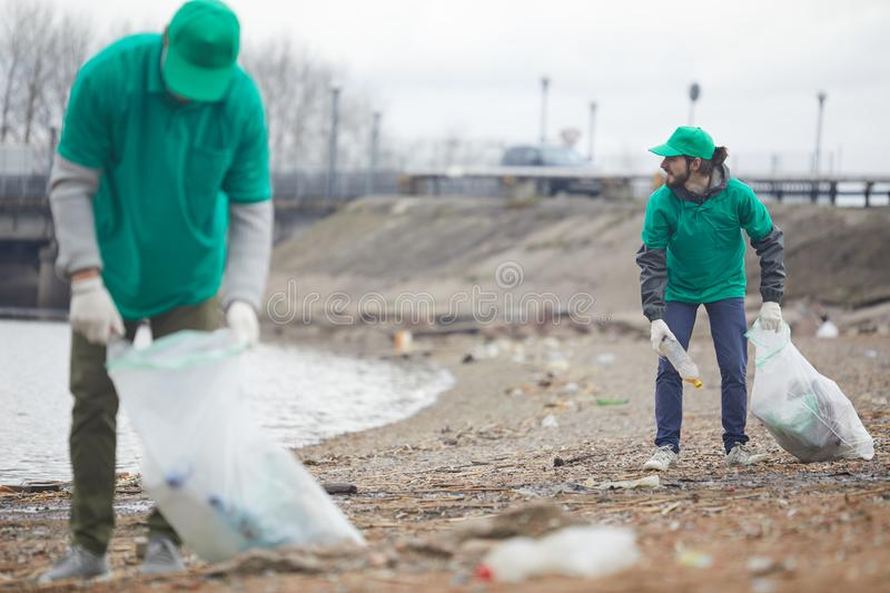 Volunteers picking litter on shore. Volunteers in green uniform working and collecting garbage on shore in cloudy day royalty free stock photos