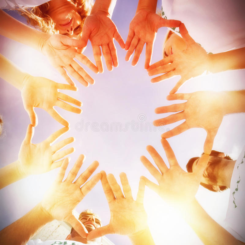 Volunteers with hands together against blue sky stock photography