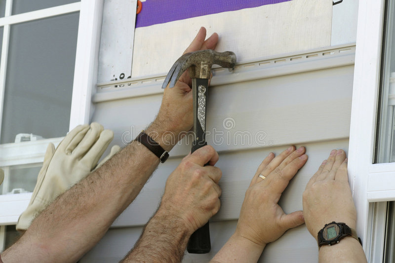 Volunteers Installing Sidiing On A New House Stock Images