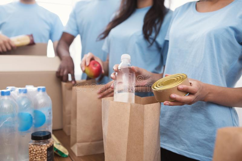 Volunteers packing food and drinks into paper bags. Homeless care. Charity team of volunteers putting food and drinks into paper bags, copy space stock photography
