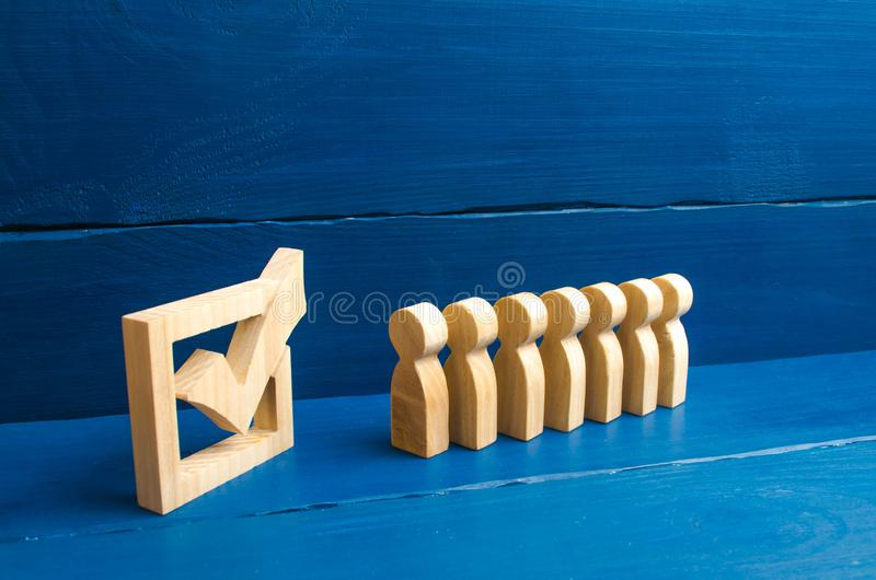 Volunteers, parties, candidates, constituency electorates. wooden human figures stand in a row next to wooden tick in the box. con stock photo