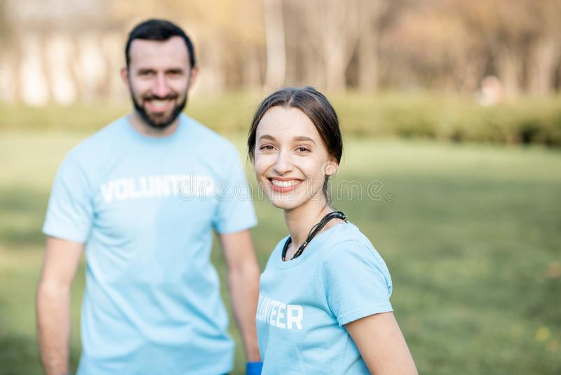 Volunteers portrait with rubbish bags in the park. Portrait of a happy volunteers in blue t-shirts in the park stock images