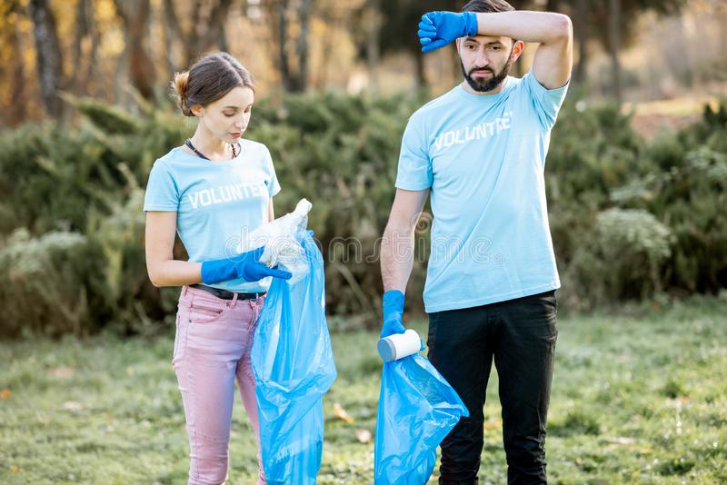 Volunteers portrait with rubbish bags in the park. Portrait of tired volunteers in blue t-shirts removing plastic rubbish in the park royalty free stock photos