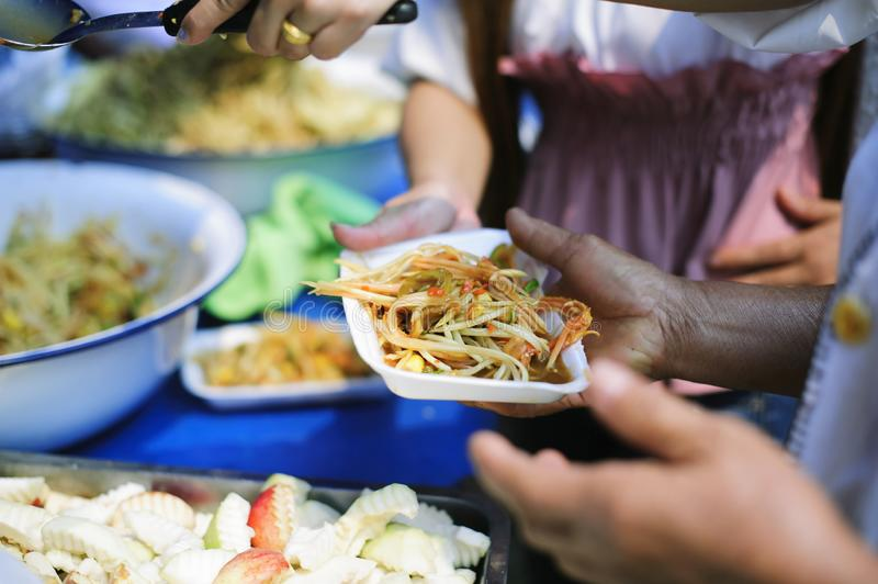 Volunteers provide food for beggars : Concepts Feeding and help : Concept of food sharing for the poor to alleviate hunger :. Volunteers Share Food to the Poor stock photo