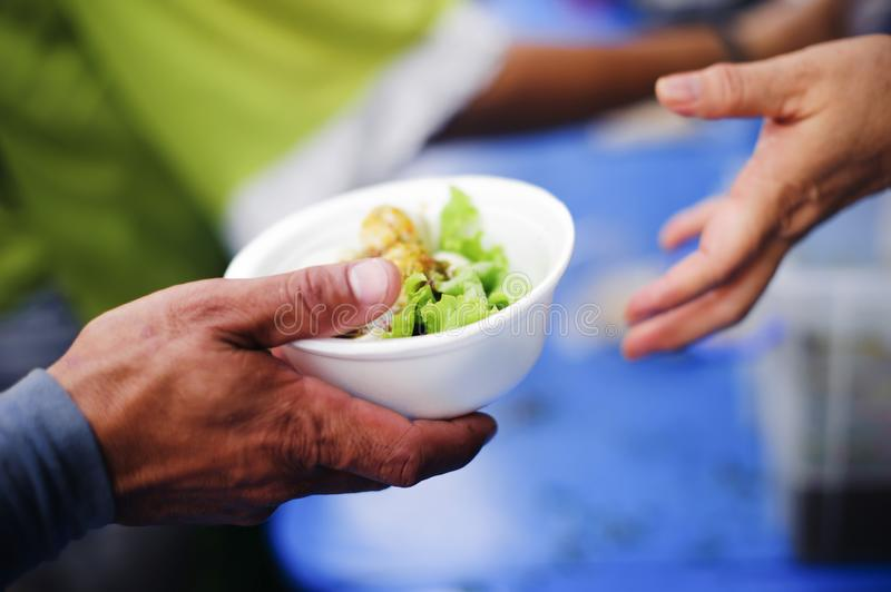 Volunteers provide food for beggars : Concepts Feeding and help : Concept of food sharing for the poor to alleviate hunger :. Volunteers Share Food to the Poor stock photos
