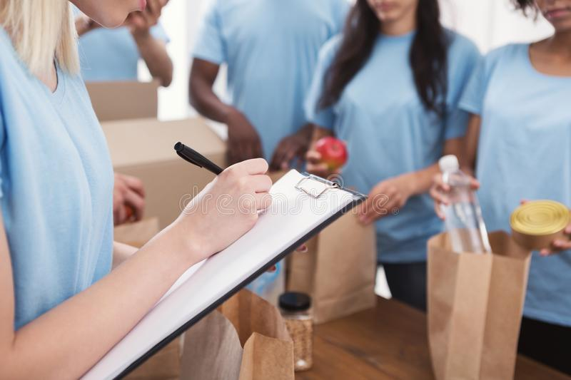 Volunteers putting food and drinks into paper bags. Donation list. Leader of volunteers writing on clipboard, checking in office, copy space stock photos