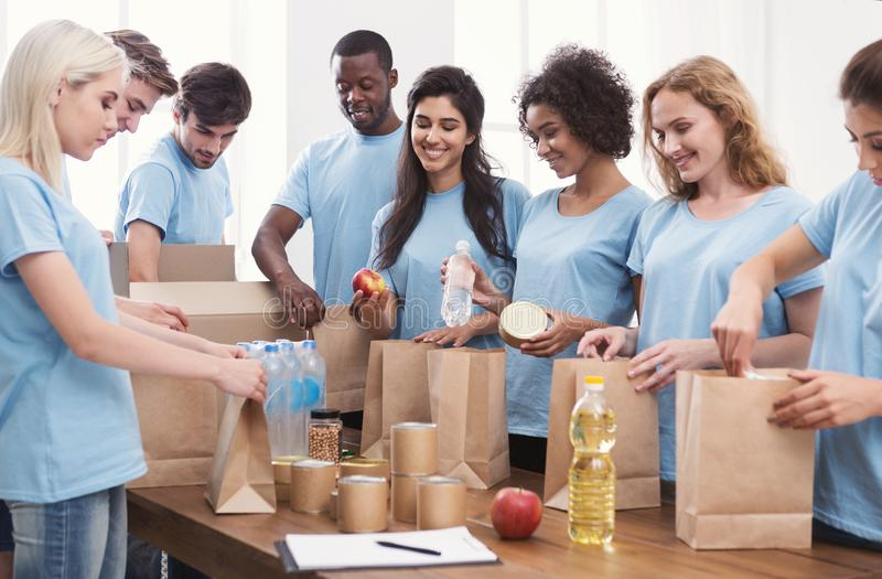 Volunteers putting food and drinks into paper bags royalty free stock photos