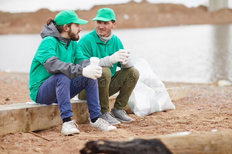 Volunteers resting on shore. Two volunteers in green uniform sitting with paper cups and resting on polluted shore royalty free stock photo