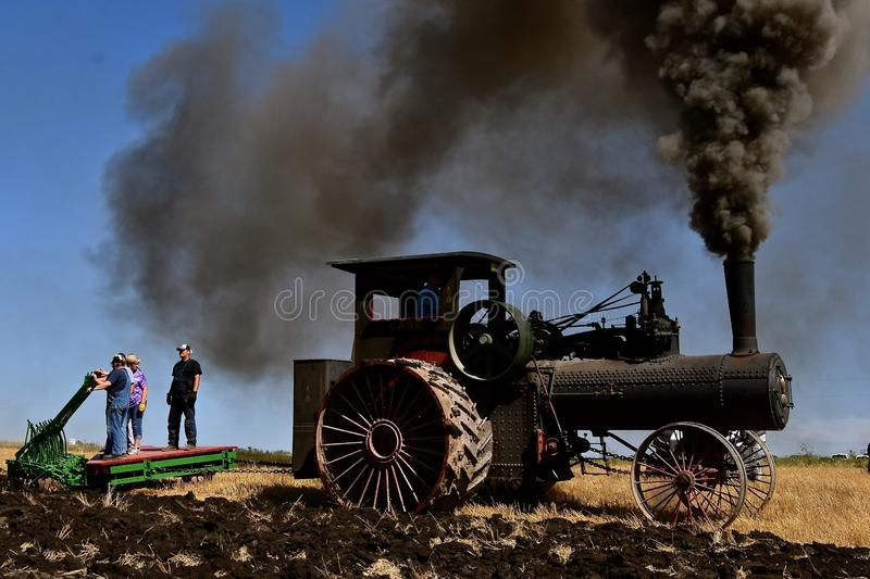Volunteers ride a gang plow pulled by a steam engine. ROLLAG, MINNESOTA, September 1, 2018: Unidentified volunteers ride a gang Verityplow pulled by a steam stock photo