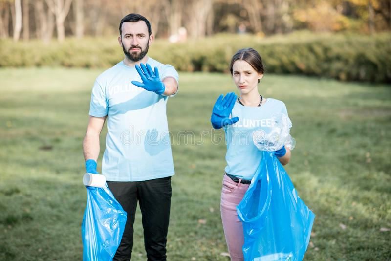 Volunteers with rubbish bags showing stop with hands. Portrait of a man and woman volunteers in blue t-shirts with rubbish bags showing stop with hands worried royalty free stock images