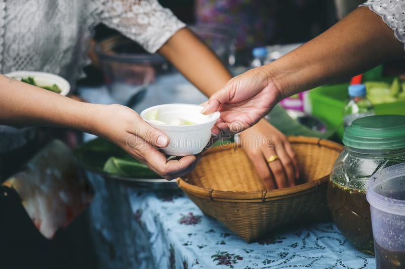 Volunteers serving food for poor people : concept of free food serving.  stock photography