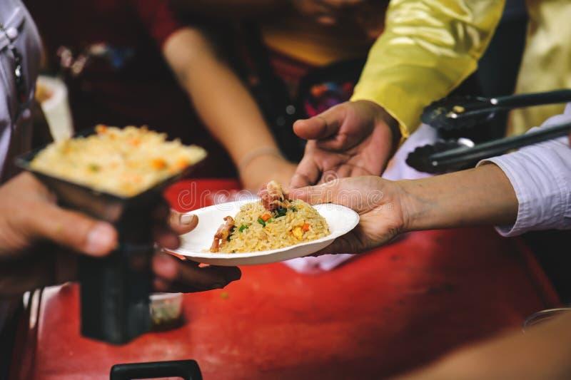 Volunteers serving food for poor people : concept of free food serving.  stock photo