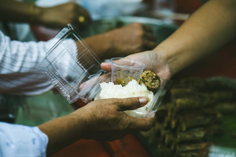 Volunteers serving food for poor people : concept of free food serving.  stock photos