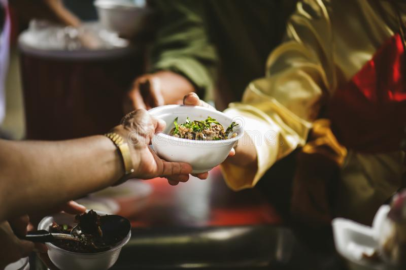 Volunteers serving food for poor people : concept of free food serving.  stock image