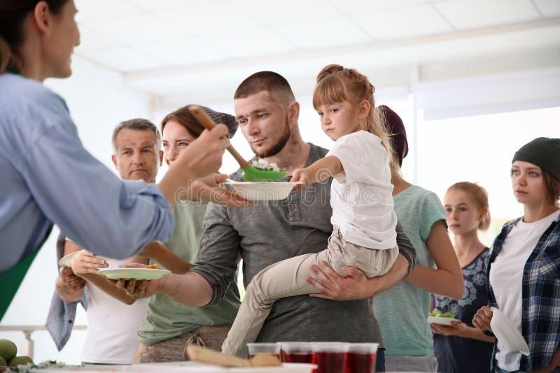 Volunteers serving food for poor people. Indoors stock photos