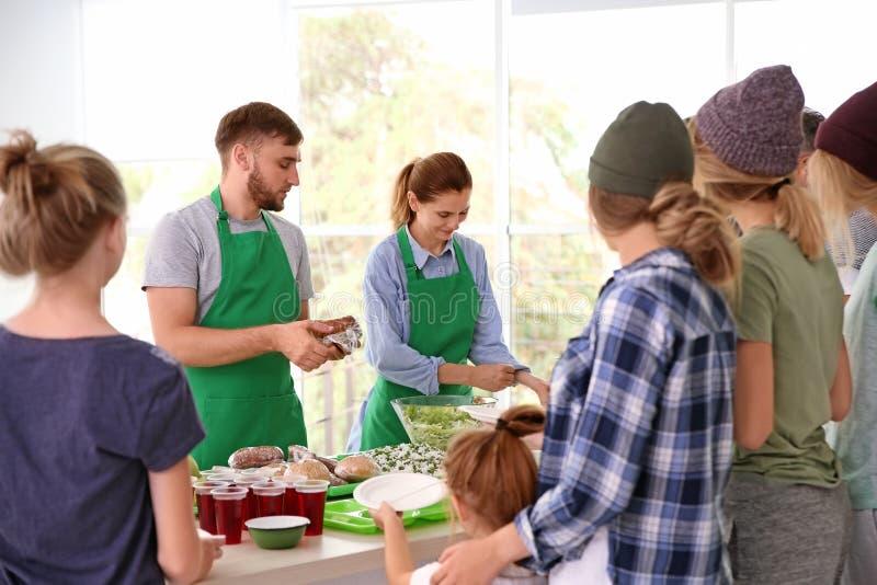 Volunteers serving food for poor people. Indoors royalty free stock photography