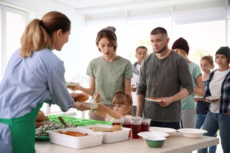Volunteers serving food for poor people royalty free stock photo