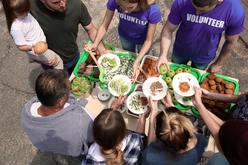 Volunteers serving food for poor people outdoors. Above view royalty free stock photos
