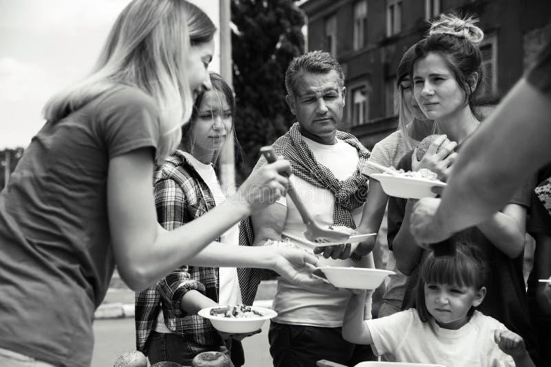 Volunteers serving food for poor people outdoors stock images