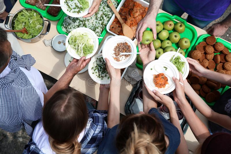 Volunteers serving food for poor people outdoors. Top view royalty free stock images