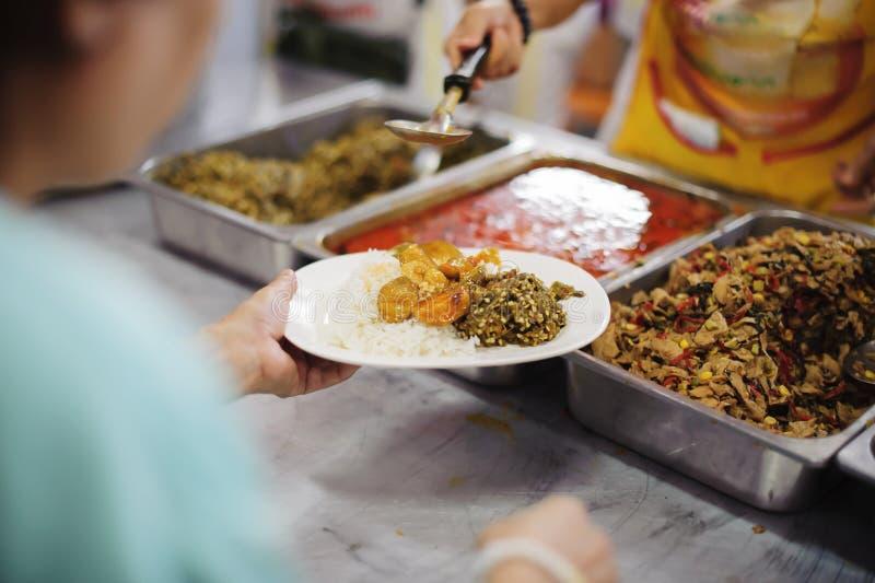 Volunteers serving food for poor people : Food sharing concept.  stock image