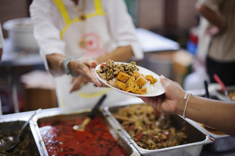 Volunteers serving food for poor people : Food sharing concept.  stock photography