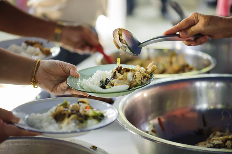Volunteers serving food for poor people : Food sharing concept.  stock photos