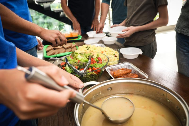 Volunteers serving food to poor people in charity centre royalty free stock photography
