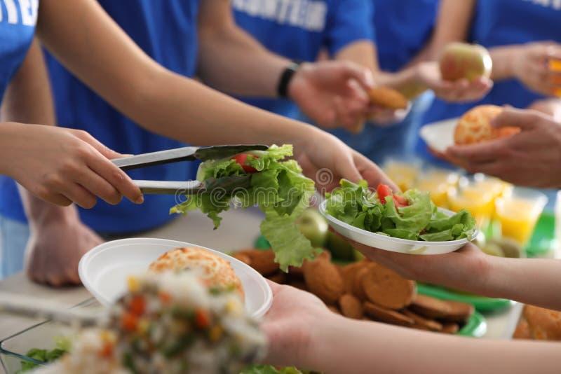 Volunteers serving food to poor people, stock photos
