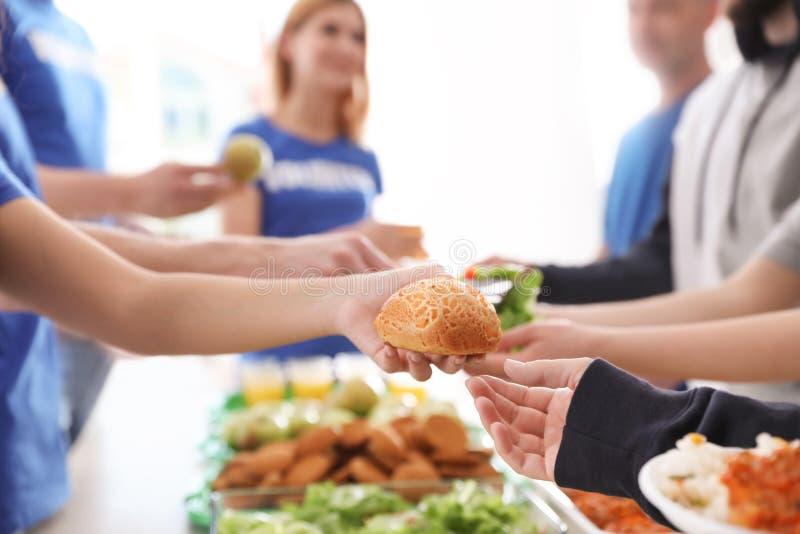 Volunteers serving food to poor people stock images
