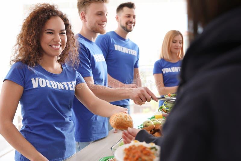 Volunteers serving food to poor people royalty free stock image