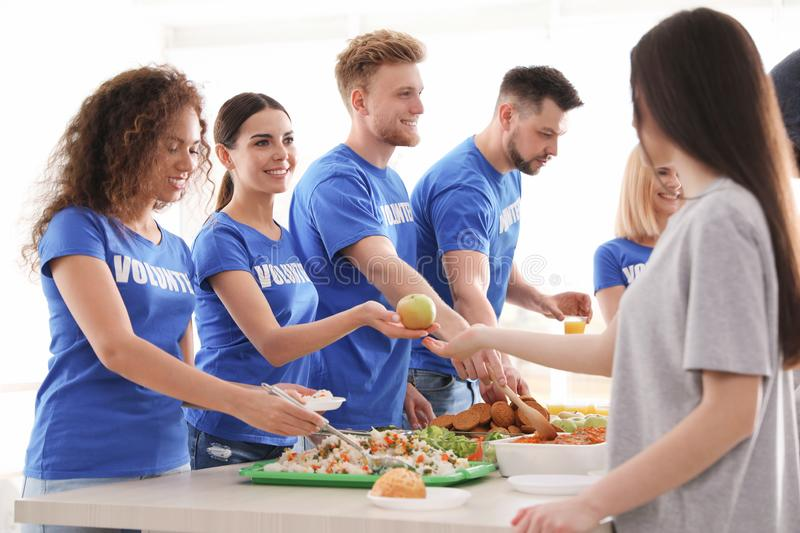 Volunteers serving food to  people indoors royalty free stock photography