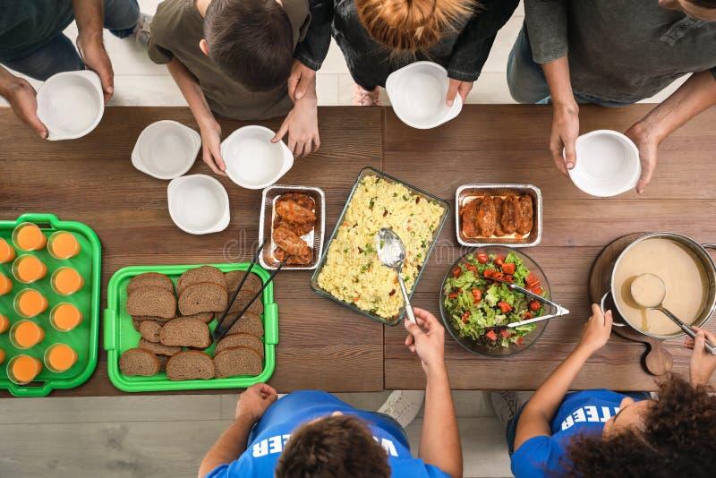 Volunteers serving food to poor people indoors stock photography