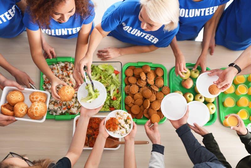 Volunteers serving food to poor people at table royalty free stock photo