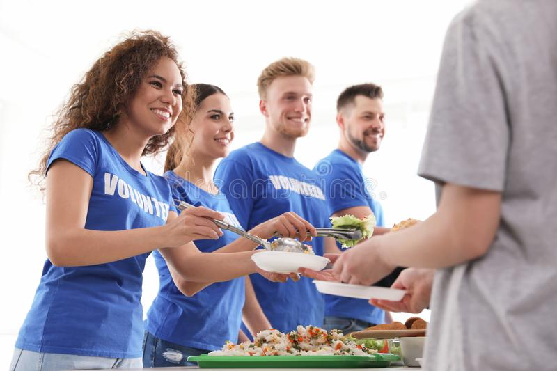 Volunteers serving food to poor people. Indoors stock photos