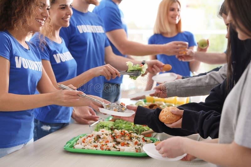 Volunteers serving food to poor people. Indoors royalty free stock photos