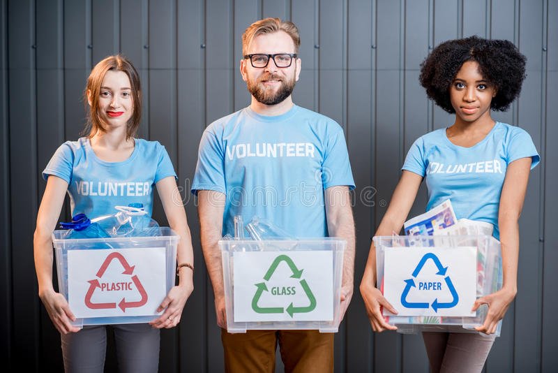 Volunteers with sorted waste. Portrait of three multi ethnic volunteers holding containers with sorted waste standing indoors stock photos