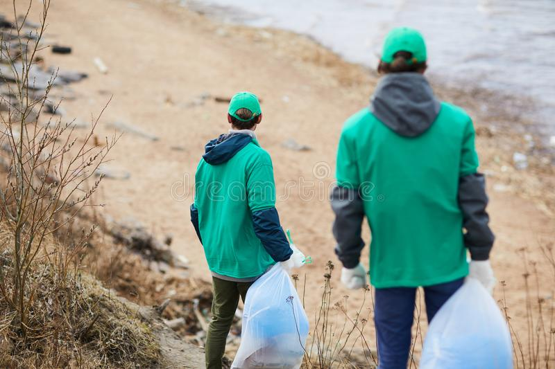 Volunteers walking to polluted shore. Back view of unrecognizable activists in green uniform walking to polluted shore with garbage bags stock photos